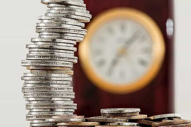 home based business pile of coins with clock in background